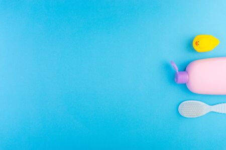 Flat lay composition of baby care products on a blue background. View from above shampoo or shower bottle gel, cleaning brush and yellow rubber toy duck