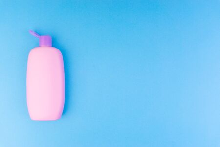 Flat lay composition of baby care products on a blue background. View from above shampoo or shower bottle gel