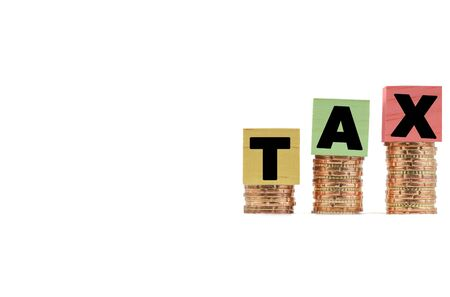 TAX Concept with colorful wooden block on stacked coins and white background