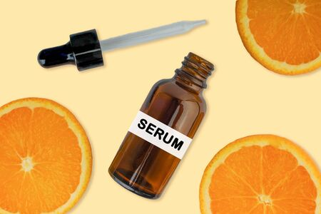 Vitamin C serum in cosmetic bottle with dropper, sliced orange on white background. Health care concept