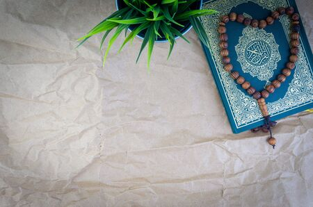 Flat lay Holy Quran with arabic calligraphy meaning of Al Quran and tasbih or rosary beads over wooden paper background. Selective focus and crop fragment Stok Fotoğraf