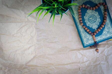 Mise à plat du Saint Coran avec une calligraphie arabe signifiant Al Coran et des perles de tasbih ou de chapelet sur fond de papier en bois. Mise au point sélective et fragment de recadrage