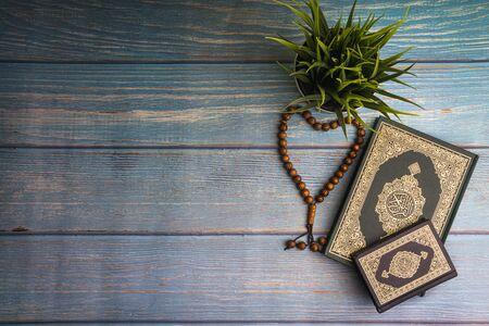 Vue à plat du vase, du tasbih ou des perles de chapelet et du livre sacré du Coran avec la signification de la calligraphie arabe d'Al Coran sur fond de papier en bois. Mise au point sélective et fragment de recadrage