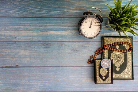 Vue à plat du vase, du tasbih ou des perles de chapelet, de la boussole, de l'horloge et du livre sacré d'Al Quran avec la signification de la calligraphie arabe d'Al Quran sur fond de bois. Mise au point sélective et fragment de recadrage Banque d'images