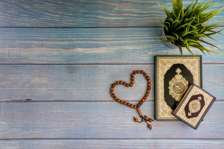 Flat lay view of vase, tasbih or rosary beads and Holy book of Al Quran with arabic calligraphy meaning of Al Quran over wooden background. Selective focus and crop fragment