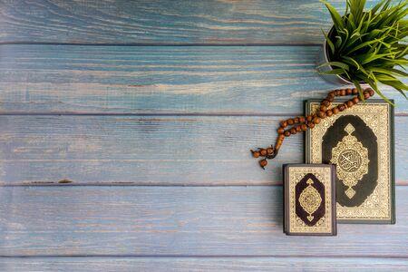 Vue à plat du vase, du tasbih ou des perles de chapelet et du livre sacré d'Al Quran avec la signification de la calligraphie arabe d'Al Quran sur fond de bois. Mise au point sélective et fragment de recadrage