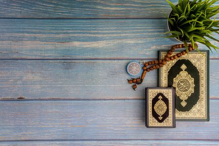 Flat lay view of vase, tasbih or rosary beads, compass and Holy book of Al Quran with arabic calligraphy meaning of Al Quran over wooden background. Selective focus and crop fragment