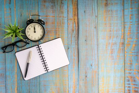 Minimalist flat lay composition of book, fountain pen, plant, vintage clock and glasses on the wooden table top view Stok Fotoğraf