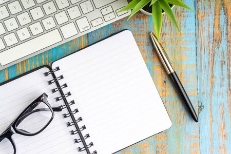 Minimalist flat lay composition of book, fountain pen, plant and glasses on the wooden table top view Stok Fotoğraf