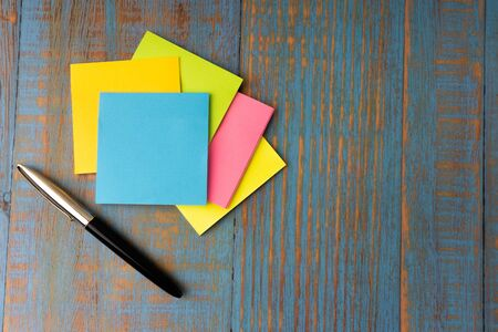 Minimalist flat lay composition of fountain pen and sticky notes on the wooden table top view. Copy space concept