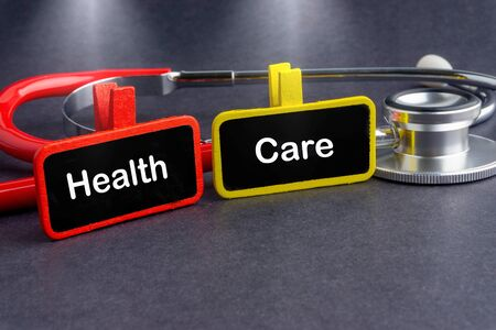 HEALTH CARE. Medicine concept. Blackboard with word HEALTH CARE and stethoscope