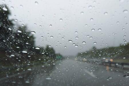 Rain drop falling on car windshield, drive car on street in city in heavy rain