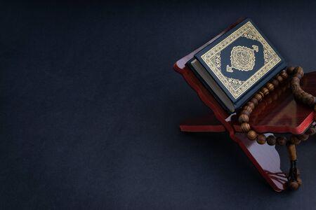 Heilige Al Quran met geschreven Arabische kalligrafie betekenis van Al Quran en tasbih of rozenkrans kralen op zwarte achtergrond. Selectieve focus en fragment bijsnijden Stockfoto