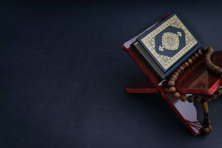 Heiliger Al Quran mit geschriebener arabischer Kalligraphiebedeutung von Al Quran und tasbih oder Rosenkranzperlen auf schwarzem Hintergrund. Selektiver Fokus und Zuschneidefragment Standard-Bild