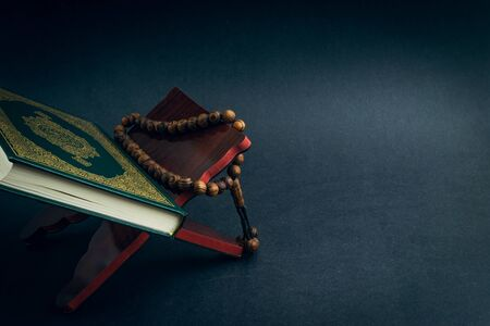 Saint Al Coran avec calligraphie arabe écrite signifiant Al Coran et tasbih ou chapelet sur fond noir. Mise au point sélective et fragment de recadrage