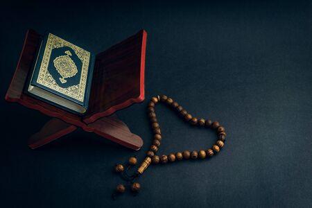 Heiliger Al Quran mit geschriebener arabischer Kalligraphiebedeutung von Al Quran und tasbih oder Rosenkranzperlen auf schwarzem Hintergrund. Selektiver Fokus und Zuschneidefragment