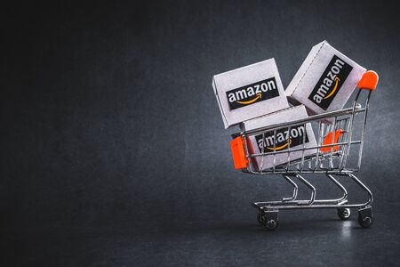 Kuala Lumpur, Malaysia - January 29, 2020 : Amazon shipping packages boxes and shopping cart on black background. Copy space and Online sales concept