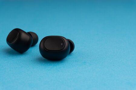 Wireless earbuds or earphones on blue background Stok Fotoğraf