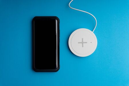 Smartphone charging on a charging pad or dock on blue background. Wireless charging