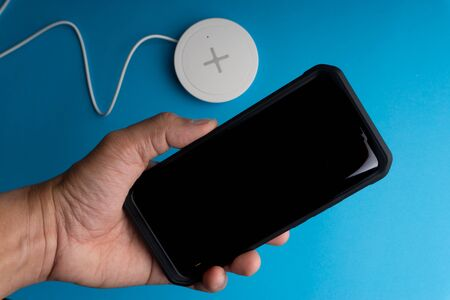 Smartphone charging on a charging pad or dock on blue background.Wireless charging and copy space