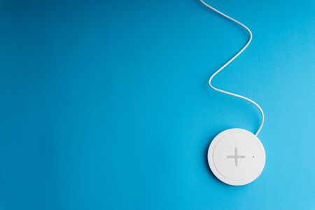 Charging pad or dock on blue background.Wireless charging and copy space  Stok Fotoğraf