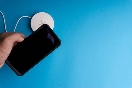 Smartphone charging on a charging pad or dock on blue background.Wireless charging and copy space  Stok Fotoğraf