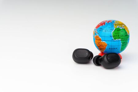 Wireless earbuds or earphones and toy globe on white background. Copy space and technology concept