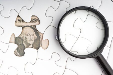 US Dollar banknotes and magnifying glass on white jigsaw puzzle. Business and copy space concept