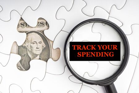 TRACKING YOUR SPENDING text with Dollar banknotes on white jigsaw puzzle. Business and copy space concept
