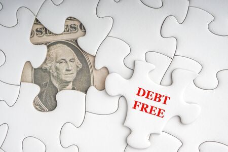 DEBT FREE text with Dollar banknotes on white jigsaw puzzle. Business and copy space concept