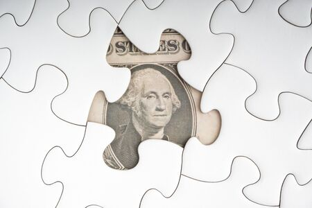 US Dollar banknotes on white jigsaw puzzle. Business and copy space concept