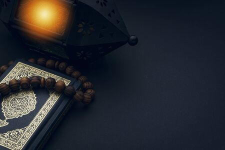 Holy Al Quran with written arabic calligraphy meaning of Al Quran and rosary beads or tasbih on black background. Copy space and crop fragment Banque d'images