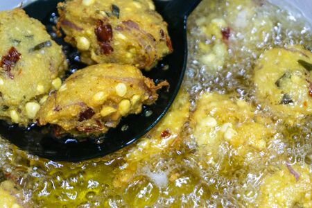 Fried cook of  Batate Vade, Batate Vadey, Fried Dhal Beans Cake or Kuih Vadey closeup. Indian traditional food. Selective focus