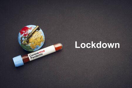 CORONAVIRUS LOCKDOWN text with world globe, key and Blood test vacuum tube on black background. Covid-19 or Coronavirus Concept 版權商用圖片