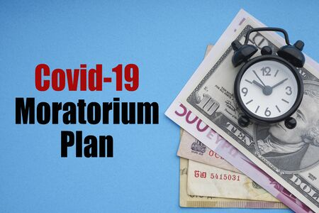 COVID19 MORATORIUM PLAN text with alarm clock and banknotes currencies on blue background. Coronavirus Covid19 and Business Concept