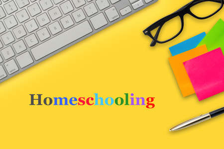 HOMESCHOOLING text with computer keyboard, eyeglasses, sticky notes and fountain pen on yellow background. Business and education concept