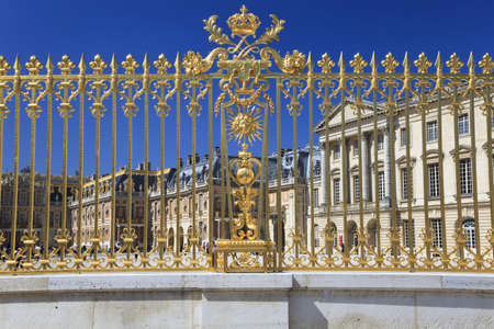 Golden fence and Palace facade in Versailles over blue sky. France