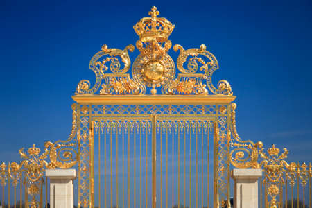 Golden Gates of the Palace of Versailles over blue sky. France Stock Photo