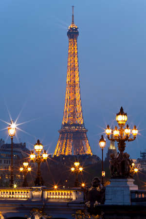 PARIS – MARCH 28: Night illumination on the bridge of Alexander III and the Eiffel Tower on March 28, 2011 in Paris. This illumination admire 25,000,000 tourists a year.