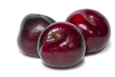 Three ripe plums isolated on white background.