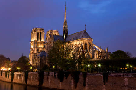Notre Dame de Paris at night. View on cathedral across the Seine river. photo