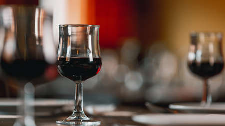 Glasses of red wine stand on a served table in a restaurant.