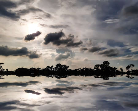 At sunset, the village environment of India, the blue sky reflects the black and white clouds and the water reflects the shadows of the clouds.
