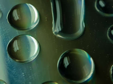 Water drops CD discs reflecting light. This light is blue, yellow and green.
