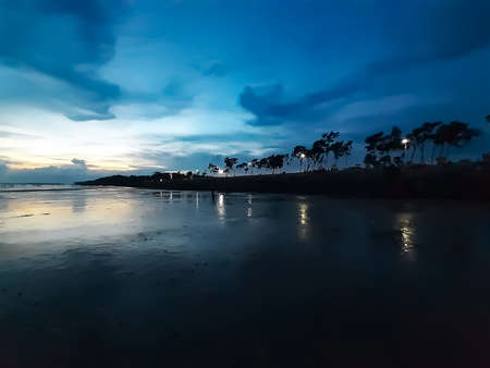 The beauty of India's long sea at sunset. Black clouds in the blue sky and the reflection of red sunlight.