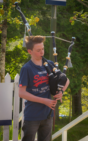 Portree, Scotland - 29 July, 2016 : A yound scotish boy playing traditional bagpipe at Portree, Scotland