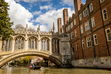 CAMBRIDGE, ENGLAND - April 17, 2016: People punting on the Cam River, passing under the Bridge of Sighs over the River at St Johns University College, Cambridge
