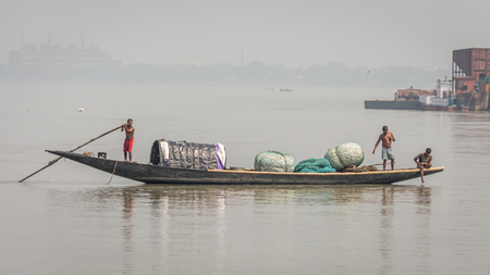 Kolkata, India - 4 March 2018: An isolated boat on river Hooghly with poor fishermen hunting for fishes as part of their daily life. These boats are widely used as mode of transportation as well in India. Editorial