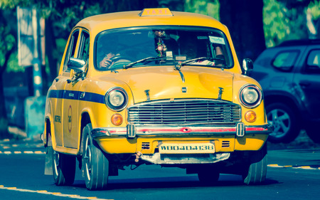 Kolkata, India - March 11th 2018: Iconic yellow taxi in Calcutta ( Kolkata ) India. The Ambassador taxi is no more built by Hindustan Motors but thousands still remain on the streets of many India