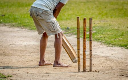 A young Indian boy playing cricket. View of a right handed batsman with all three stumps visible.
